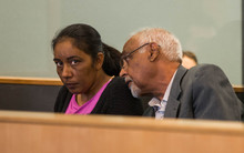 Amandeep Kaur (left) sitting in the dock at the Auckland High Court with a translator (right).