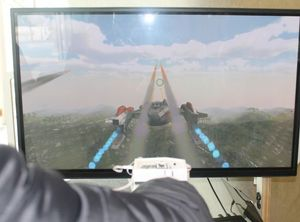 View along the arm of a gamer wearing the haptic feedback glove as he plays the flight simultor