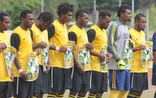Vanuatu players hold signs honouring former international Selwyn Sese before their match against Fiji.