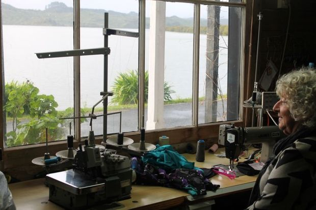 Carol sits at her sewing  machine  in the window looking on to the harbour