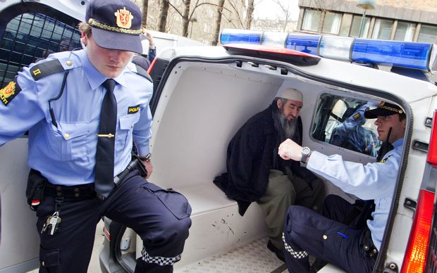 Mullah Krekar (C), sits in a police van after his arrest March 2012 at his Oslo appartment by Norwegian police
