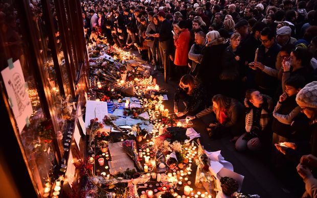 People light candles at a makeshift memorial in front of Le Carillon restaurant, one of the site of the attacks in Paris.