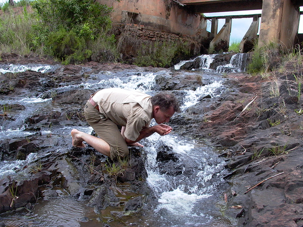 Kennedy Warne drinking from the headwaters of the Okavango River, 2003