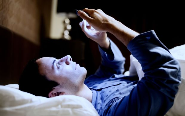 Man in bed with smartphone - blue light