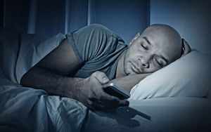 Sleeping man in bed with smartphone