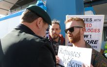 A protester stops a Defence Force member getting into the forum.
