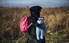 A refugee carries her child after crossing the Greek-Macedonian border near Gevgelija.