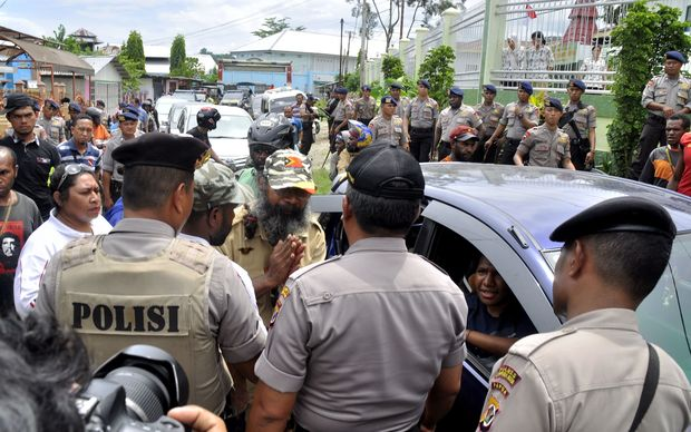 Papuan pro-independence activist Filep Karma (C) asks police for a permit to hold a convoy with his supporters after being released from prison in Abepura, Papua province, on November 19, 2015.
