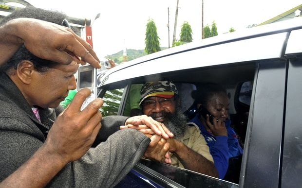 Papuan pro-independence activist Filep Karma (inside vehicle) shakes hands with his supporters after being released from prison in Abepura, Papua province, on November 19, 2015.