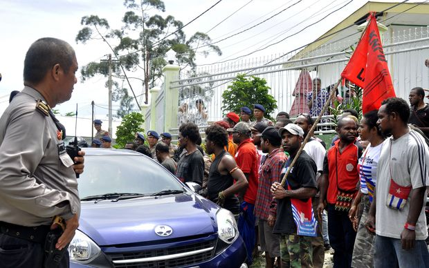 Indonesia police officer (L) stands guard as Papuan pro-independence activist Filep Karma's supporters hold a rally outside prison in Abepura, Papua province, on November 19, 2015 to welcome their leader's freedom