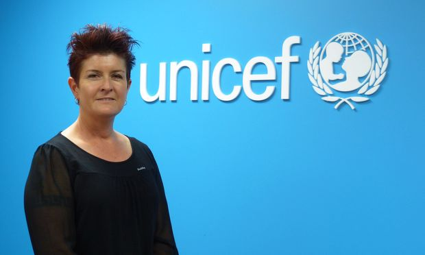 Unicef's Deborah Morris-Travers standing in form of blue wall with Unicef logo