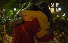 People hug in front of a memorial set up near the Bataclan theatre in Paris.