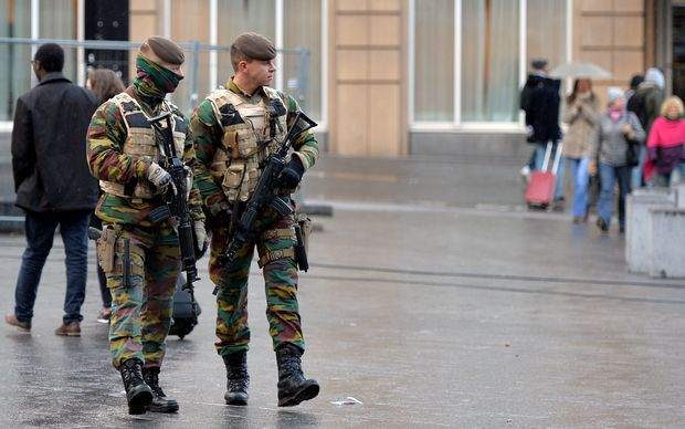 Soldiers patrol streets in Brussels as the alert status is raised to the highest level.