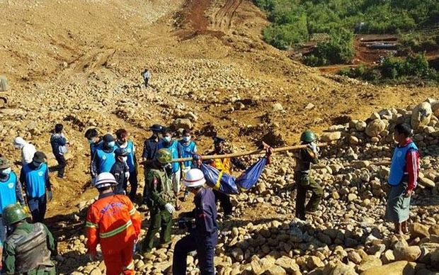 Search and rescue teams remove a body from the scene of a a huge landslide at a jade mine in northern Myanmar.