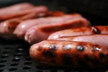 Pork sausages on a barbecue.
