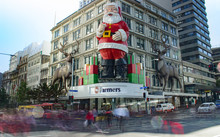 A giant Santa on Queen Street overlooks shoppers crossing the road in the Auckland Central City.