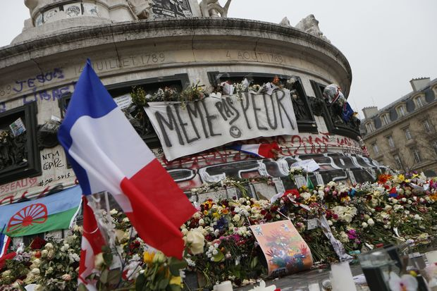 A picture taken on November 27, 2015, shows French national flags, candles and flowers at a makeshift memorial in Place de la Republique square in Paris.