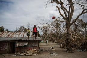 (Foreground) a child and an elderly man stand on the roof of a dwelling damaged Cyclone Pam, on Ifira Island, just off the coast of the main island of Efate.