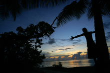 A child on Kiribati watches the sunset on an ever rising ocean.