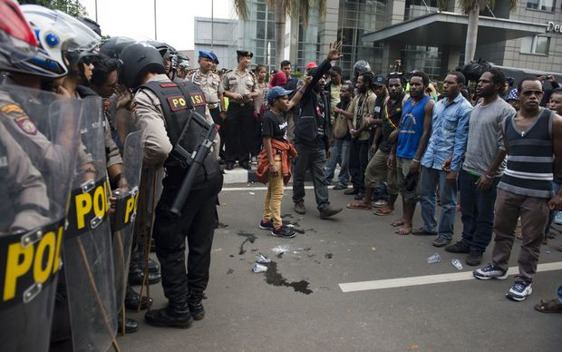 Papuan pro-independence demonstrators stage a protest while police (L) armed with tear gas guns take position in Jakarta on December 1, 2015, before police fired tear gas at a hundreds-strong crowd hurling rocks during a protest against Indonesian rule over the eastern region of Papua.