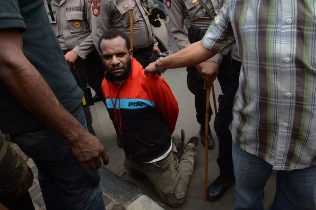 A Papuan pro-independence demonstrator is arrested by police in Jakarta on December 1, 2015 after police fired tear gas at a hundreds-strong crowd hurling rocks during a protest against Indonesian rule over the eastern region of Papua.