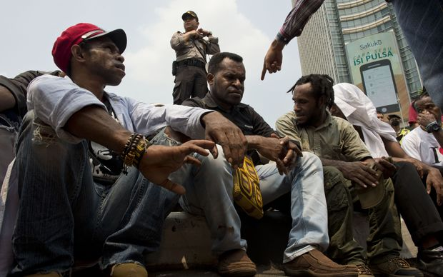 Papuan pro-independence demonstrators are arrested by police in Jakarta on December 1, 2015, after police fired tear gas at a hundreds-strong crowd hurling rocks during a protest against Indonesian rule over the eastern region of Papua.