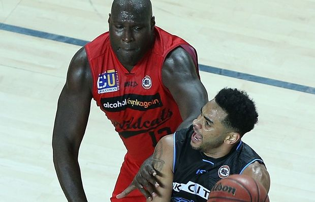 Perth player Nate Jawai defends Breakers guard Corey Webster