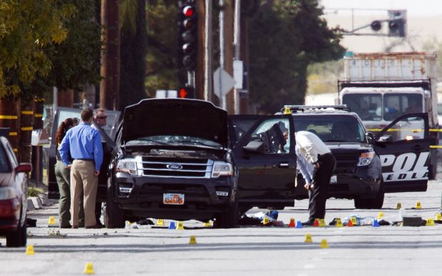 Investigators look at the vehicle involved in a shootout between police and two suspects in San Bernardino, California.