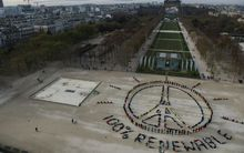 "People make the ""Pray for Paris"" sign along with the slogan ""100 percent renewable"" in Paris on the sidelines of the COP21 climate change conference."
