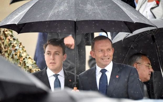 Former Australian prime minister Tony Abbott (R) and a former staffer attend a remembrance service attended by Britain's Prince Charles and Camilla, Duchess of Cambridge at the Australian War Memorial in Canberra on November 11, 2015