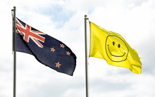 The current New Zealand flag flies alongside a flag with a smiley face on it.