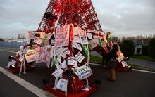 An Eiffel Tower made of bistro chairs is seen covered in messages related to climate change at COP21.