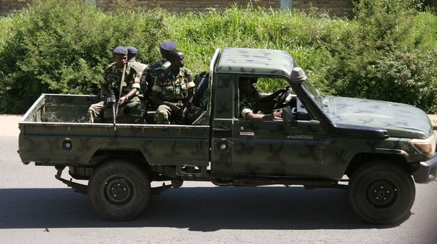 Military personnel sit aboard a vehicle driving in Bujumbura on December 11, 2015.