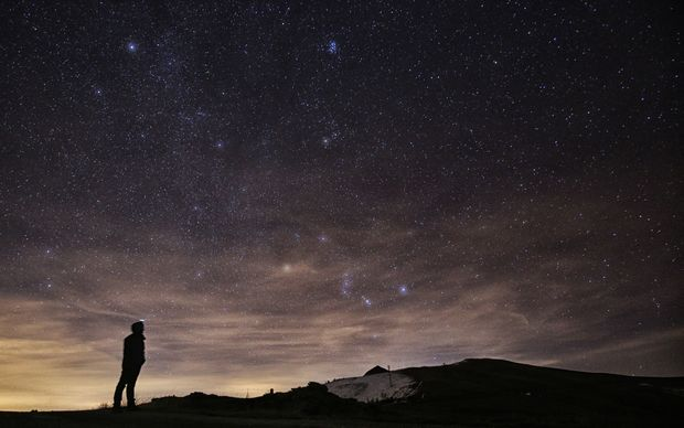 A photographer looks at the sky at night to see the annual Geminid meteor shower in northern Italy.