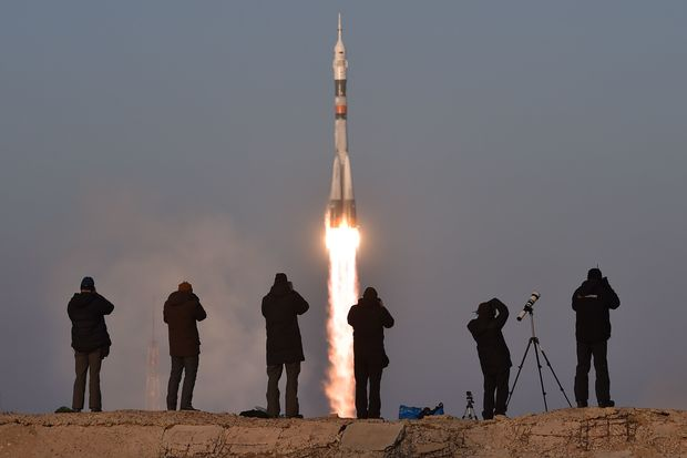 Photographers take pictures as Russia's Soyuz spacecraft blasts off.