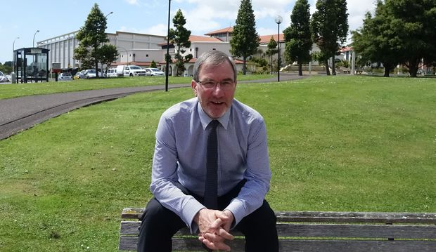Paul Spoonley sits on the back of a bench with green grass of uni behind