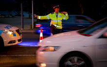 A police officer directing traffic at a alcohol check point.