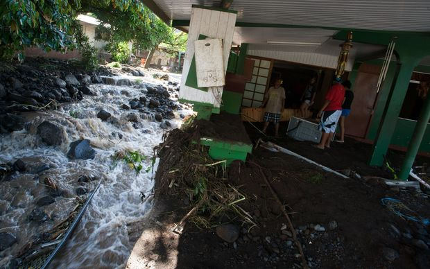 Residents inspect the damage caused by heavy rainfall and an overflow of the Ahonu river in Mahina, Tahiti, French Polynesia. December 2015.