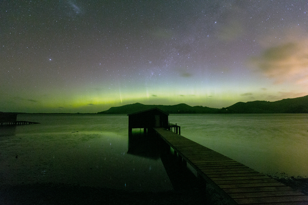 Green aurora, with a silhouetted boat shed in the foreground