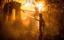 A firefighter battles a wild fire in Carrio, northwest Spain.