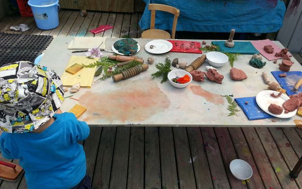 A child plays at the natural collage table at Glenn Innes Playcentre.