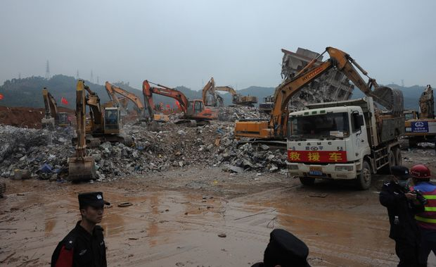 Excavators work at the site of the landslide that hit the industrial park in Shenzhen on December 22, 2015. CHINA OUT AFP PHOTO / STR