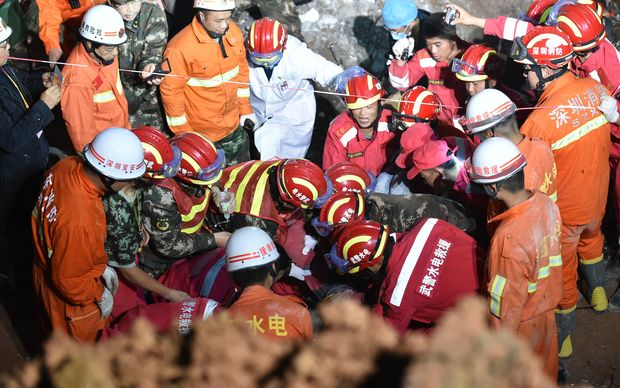 A survivor is found at the site of the landslide at an industrial park in Shenzhen, south China's Guangdong Province, Dec. 23, 2015. One man was pulled out alive early Wednesday morning more than 60 hours after a landslide in Shenzhen. (Xinhua/Liang Xu) (lfj)