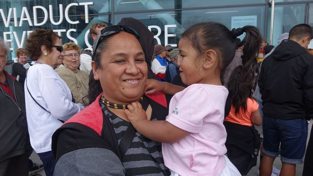 Pep Tuiasau and her daughter Marley-Jae wait in line for the Auckland City Mission Christmas lunch.
