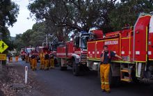 Country Fire Authority volunteer fire-fighters take a break while fighting fires which flared in a scenic area along Victoria's Great Ocean Road on Christmas Day, destroying dozens of houses.