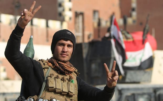 "A member of Iraq's elite counter-terrorism service flashes the ""V"" for victory sign."