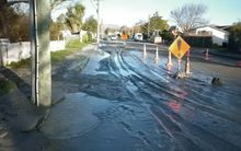 Silt and water produced by liquefaction covers a street in Avonside, Christchurch.
