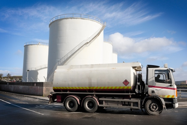 A truck with a fuel tank at an industrial storage site.