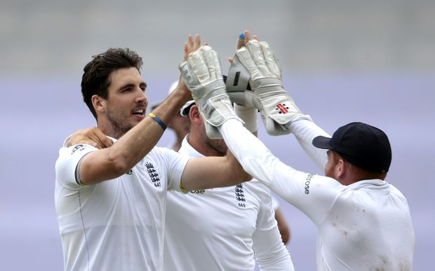England's bowler Steven Finn (L) celebrates after dismissing South African captain Hashim Amla during the fourth day of the first cricket Test at Kingsmead on Dec 29, 2015 in Durban