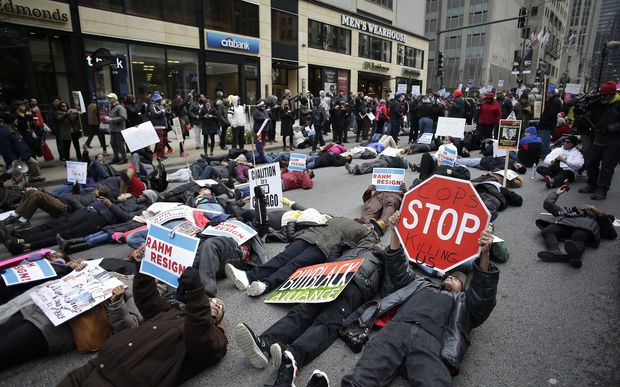 Demonstrators continue to protest the fatal police shooting of Laquan McDonald as they attempt to disrupt holiday shoppers along Chicago's Michigan Avenue.